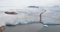 The massive calving front of the southernmost of four tributaries of Upernavik Icestream, Northwest Greenland. In the center a rising plume of sediment-laden subglacial meltwater discharge protrudes the water surface. Subglacial meltwater discharge is a major component of meltwater runoff and therefore the surface mass balance (SMB). Credit: Niels J. Korsgaard, Natural History Museum of Denmark.